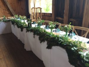 A moss-covered head table created by the Garden by the Gate Floral Design at Rivercrest Farm