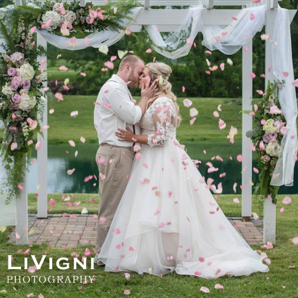 Flower covered wedding arch by the Garden by the Gate Floral Design, North Canton. Photo-Livigni Photography