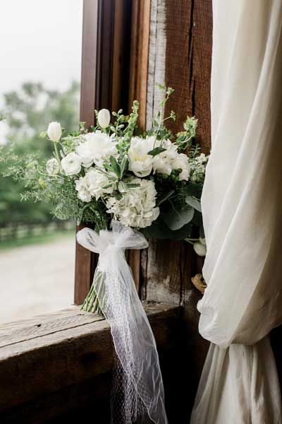 Classic white bridal bouquet with greenery by Garden by the Gate Floral Design. Venue Rivercrest Farm